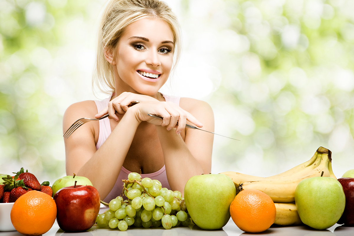 Beautiful smiling woman and fresh fruits