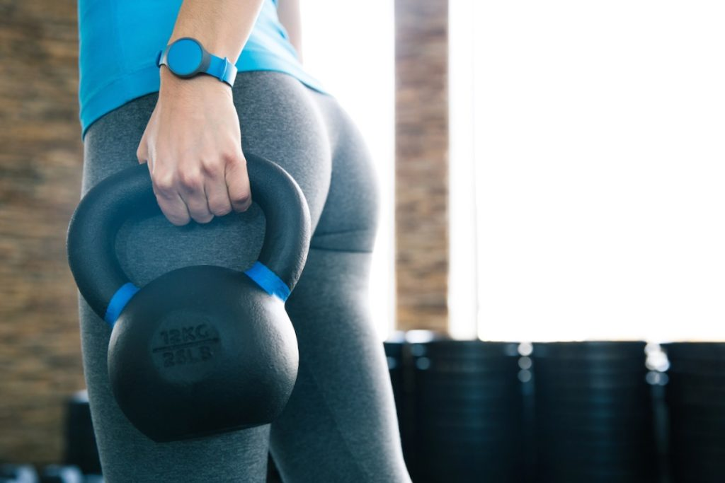 Closeup image of a woman working out with kettle ball